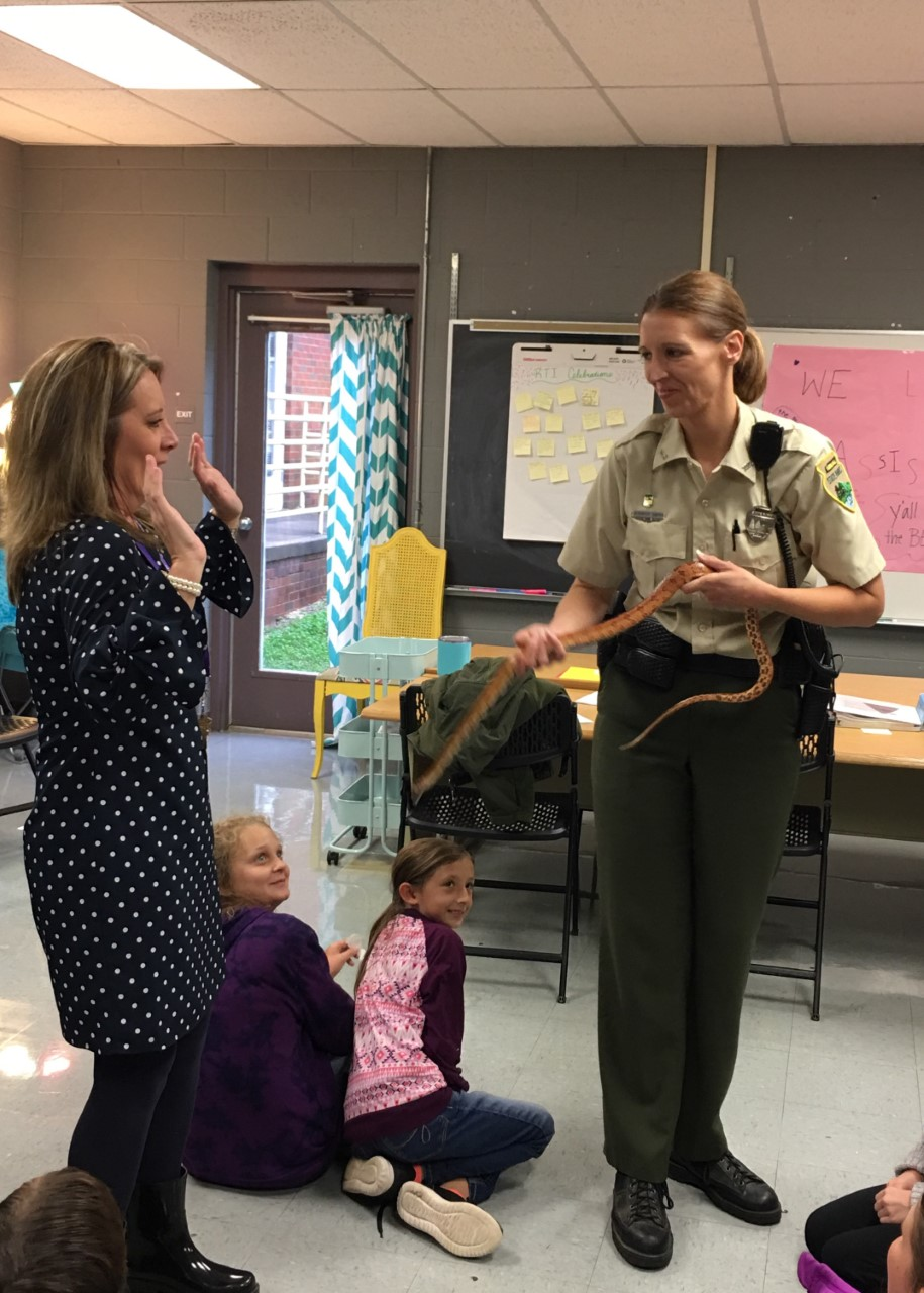 Mrs. Gilman learning about snakes from a visiting park ranger